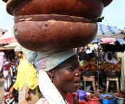 A woman hawks local soup seasoning locally known as 'Iru' in calabash, through the 'Oja Oba' market in Ilorin metropolis in Nigeria's central state of Kwara, November 6, 2012.