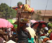 A woman carries a load bearing NURHI designed umbrella at the Monday market in Kakuri district in Nigeria's northern city of Kaduna November  12, 2012.