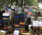 Women selling clothes wait for customers at a roadside market in Ibadan, South-west, Nigeria November 7, 2012.