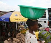 A boy hawks past a roadside makeshift kiosk with an umbrella promoting family planning at Mapo district in Ibadan, South-west, Nigeria November 7, 2012.