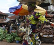 A woman hawks past a roadside market with an umbrella promoting family planning in Mapo district in Ibadan, South-west, Nigeria November 7, 2012.