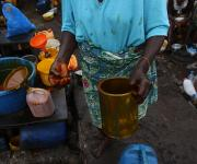 A woman working a roadside palm oil market holds a tin in Mapo district in Ibadan, South-west, Nigeria November 7, 2012.