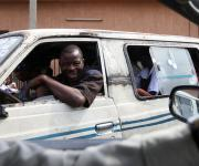 A commercial bus driver is pictured through the window frame of a car along a road in Ibadan, South-west Nigeria, November 7, 2012