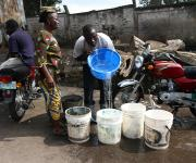 A man turns in water into a bucket as a woman watches along a road in Ibadan, South-west Nigeria, November 7, 2012