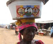 A villager carries a bowl on her head as she walks past a local market in Lugbe village in the outskirt of Nigeria's capital Abuja November 9, 2012.