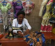 A woman works on a tailoring machine in her makeshift shop in Mpape village, outskirt of Nigeria's capital Abuja November 9, 2012.