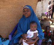 Zainab Allassan, a family planning user, sits with her baby outside her home in Jiwa village, outskirt of Nigeria's capital Abuja November 10, 2012.