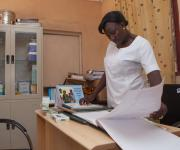 MrsTalatu Patricia Kagai, Matron in charge of Hunkuyi General Hospital, Kundan LGA, Zaria (one of the FP clinics renovated and refurbished by NURHI) observing the NHMIS records.