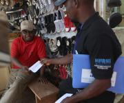 A family planning mobilizer for NURHI distributes pamphlets campaigning for family planning inside a market in Area3 at the central business district in Abuja, November 10, 2012.