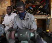 Shoe makers work in a market in Area3 at at the central business district in Abuja, November 10, 2012.
