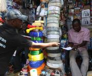 A family planning mobilizer for NURHI distributes pamphlets on family planning to traders inside a market in Area3 at the central business district in Abuja, November 10, 2012.