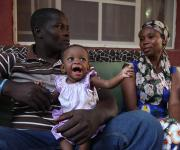 Mr and Mrs Voke Onodje Moore sits with their baby, Hannah during a testimonial interview on family planning usage with NURHI in their home in Karu village, outskirt of Nigeria's capital Abuja November 10, 2012