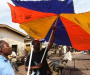 A mobilizer tries to set up a NURHI designed umbrella used for promoting family planning in an abattoir in Kakuri district in Nigeria's northern city of Kaduna, November 12, 2012.