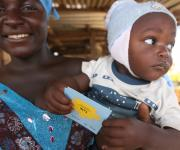 A family planning client, Anna Efe, carries her baby after collecting a referral 'Go card' from a mobilizer during a street visibility parade in Romi market in Nigeria's northern city of Kaduna, November 12, 2012.