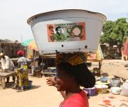 A woman, Maman Joy carries a bowl with old printed Nigerian Naira at Romi market in Nigeria's northern city of Kaduna, November 12, 2012.