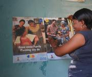 A family planning mobilizer pastes promotion posters on a wall before the start of a mobility parade in Orolodo primary health centre in Omuaran township in Nigeria's central state of Kwara, November 5, 2012.