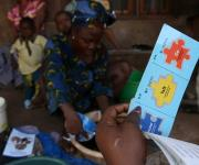 A family planning mobilizer prepares to tear off a copy of 'Go card' to a client during a visibility parade near Orolodo primary health centre in Omuaran township in Nigeria's central state of Kwara, November 5, 2012.