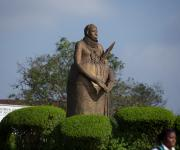 The graceful giant statute of a Benin King in his full regalia standing in the heart of the city
